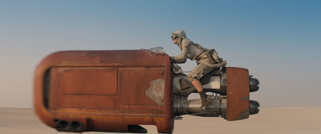 Rey zooms on her speeder through Jakku's desert